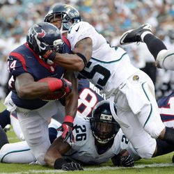 Houston Texans running back Ben Tate, left, scores a touchdown against pressure from Jacksonville Jaguars free safety Dawan Landry (26) and strong safety Dwight Lowery, right, during the first half of an NFL football game, Sunday, Sept. 16, 2012, in Jacksonville, Fla.