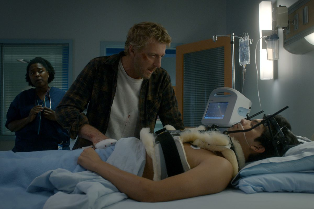 Johnny Lawrence pleads with a comatose Miguel, who is laying in a hospital bed with a brace strapped to his shoulders and head