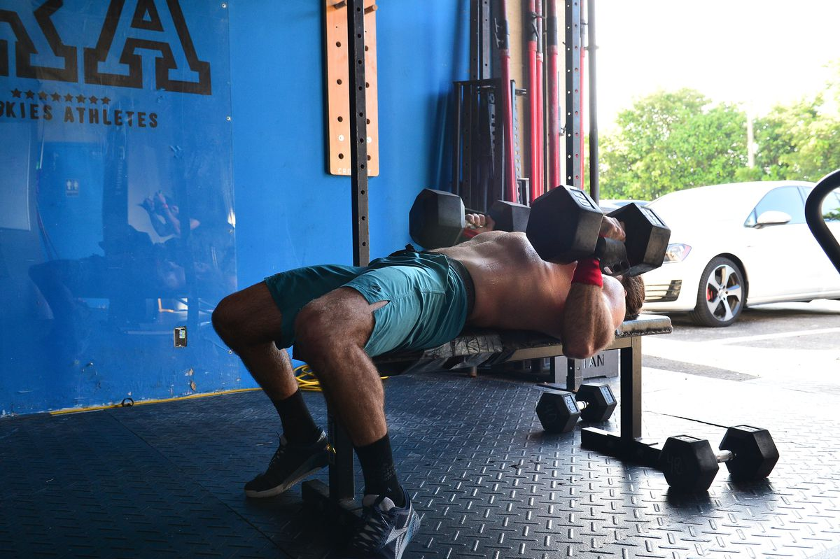 A CrossFitter lifts a dumbbell during a socially distanced workout class