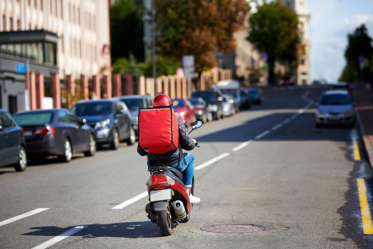 Person on motorcycle with red delivery box behind them, driving down an open city road