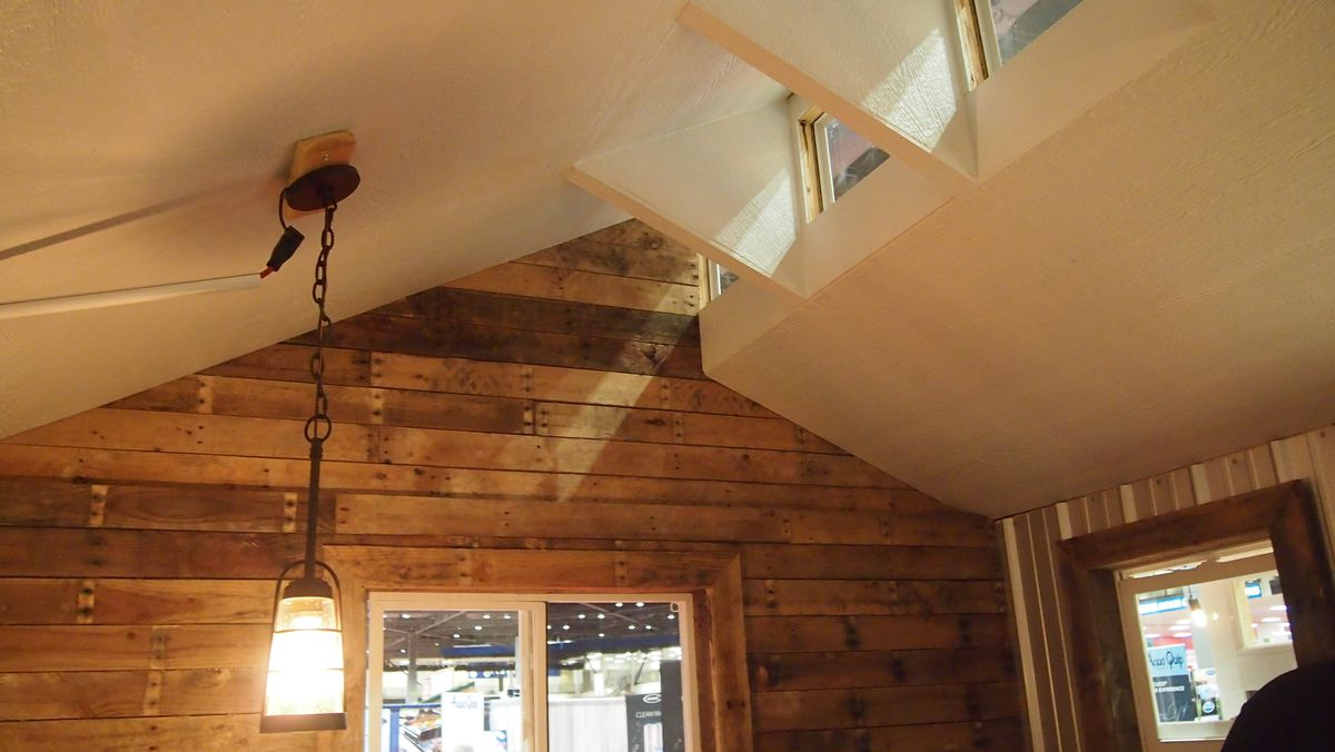 A wood wall leads up to a vaulted ceiling and skylights