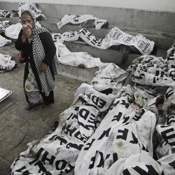 A woman looks for her missing family member at a morgue in Karachi, Pakistan, Wednesday, Sept. 12, 2012. Pakistani officials say the death toll from devastating factory fires that broke out in two major cities has killed hundreds.