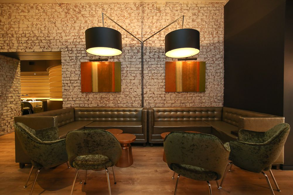 A photo of a lounge space with four chairs and two over hanging lights at RIoja