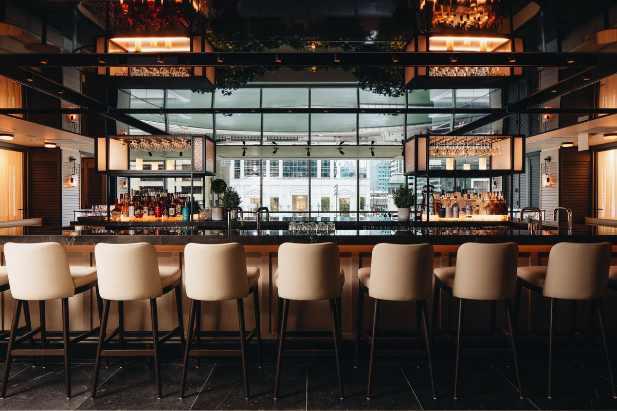 A bar with seven white, leather stools with backs, and plenty of liquor in the back.