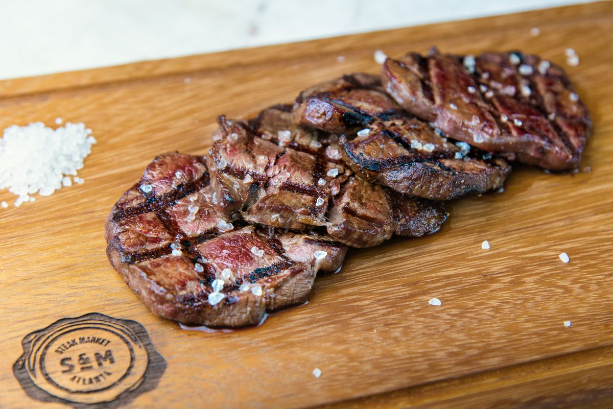 Four grilled steak filets laid out on a Steak Market-branded wooden cutting board in Atlanta
