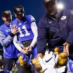 Brigham Young athletic director Tom Holmoe, quarterback Zach Wilson (11) and head coach Kalani Sitake celebrate after their win over the Western Michigan Broncos in the Famous Idaho Potato Bowl at Albertsons Stadium in Boise, Idaho on Friday, Dec. 21, 2018.