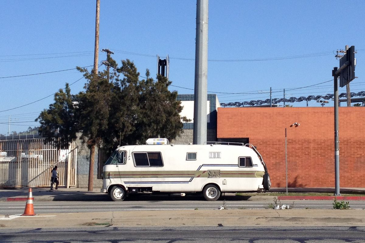 An RV parked in an industrial area.