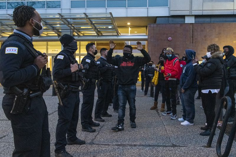 Community activist Ja'Mal Greene walks up and down a police line with his hands up outside Chicago Police Headquarters, during a protest in response to the release of the body camera footage that shows police killing Adam Toledo in late March, Thursday, April 15, 2021. | Tyler LaRiviere/Sun-Times