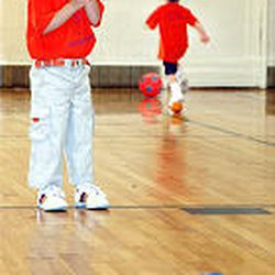 Maya Squire contemplates kicking a soccer ball as part of the Start Smart Sports Development Program. The program helps children develop skills and prepare for organized sporting activities in the schools.