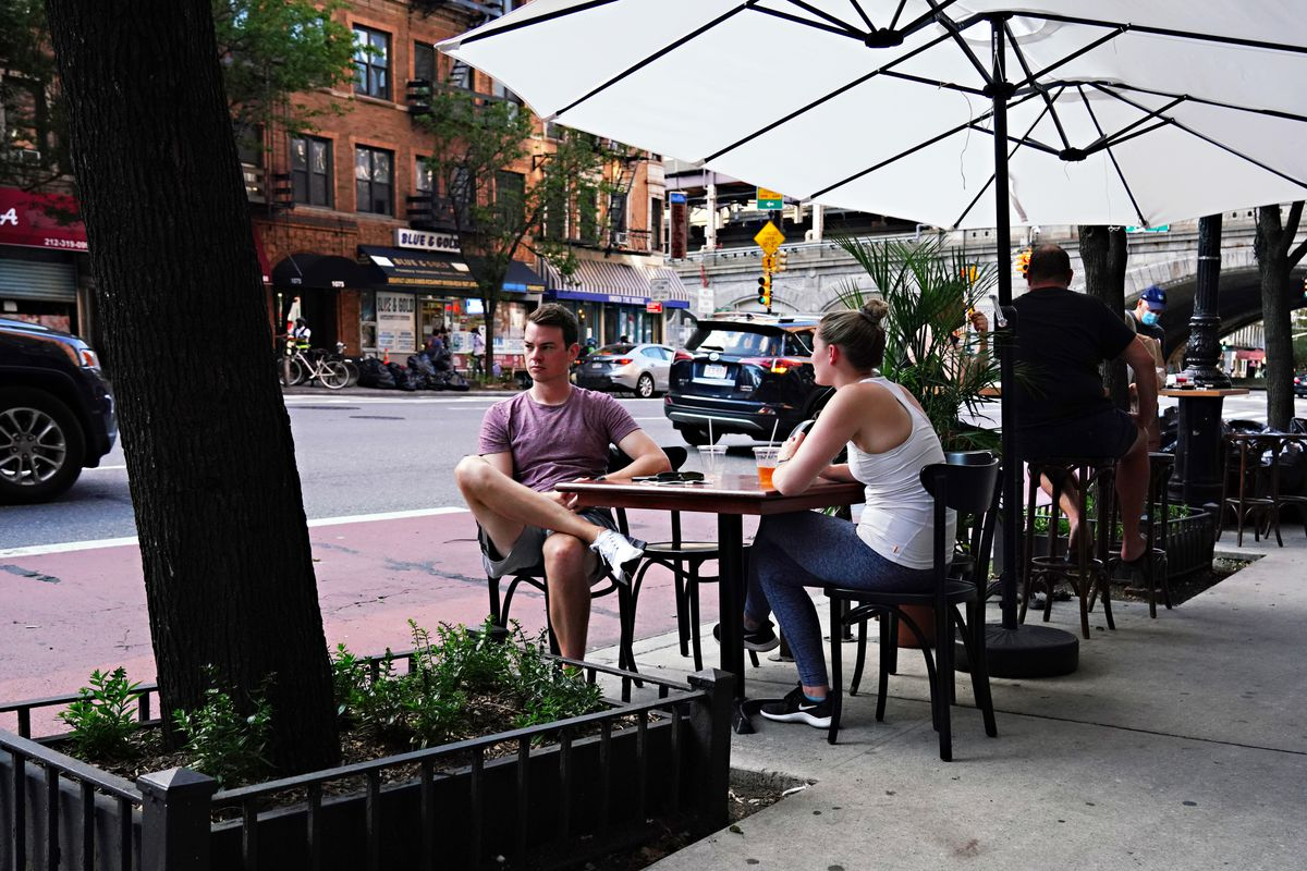 Two people sit in a temporary outdoor dining area as New York City moves into Phase 3 of re-opening following restrictions imposed to curb the coronavirus pandemic on July 13, 2020.