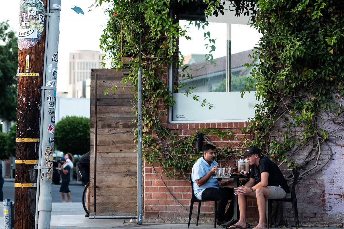 A pair of diners sit next to a brick wall at an outdoor table in Los Angeles.