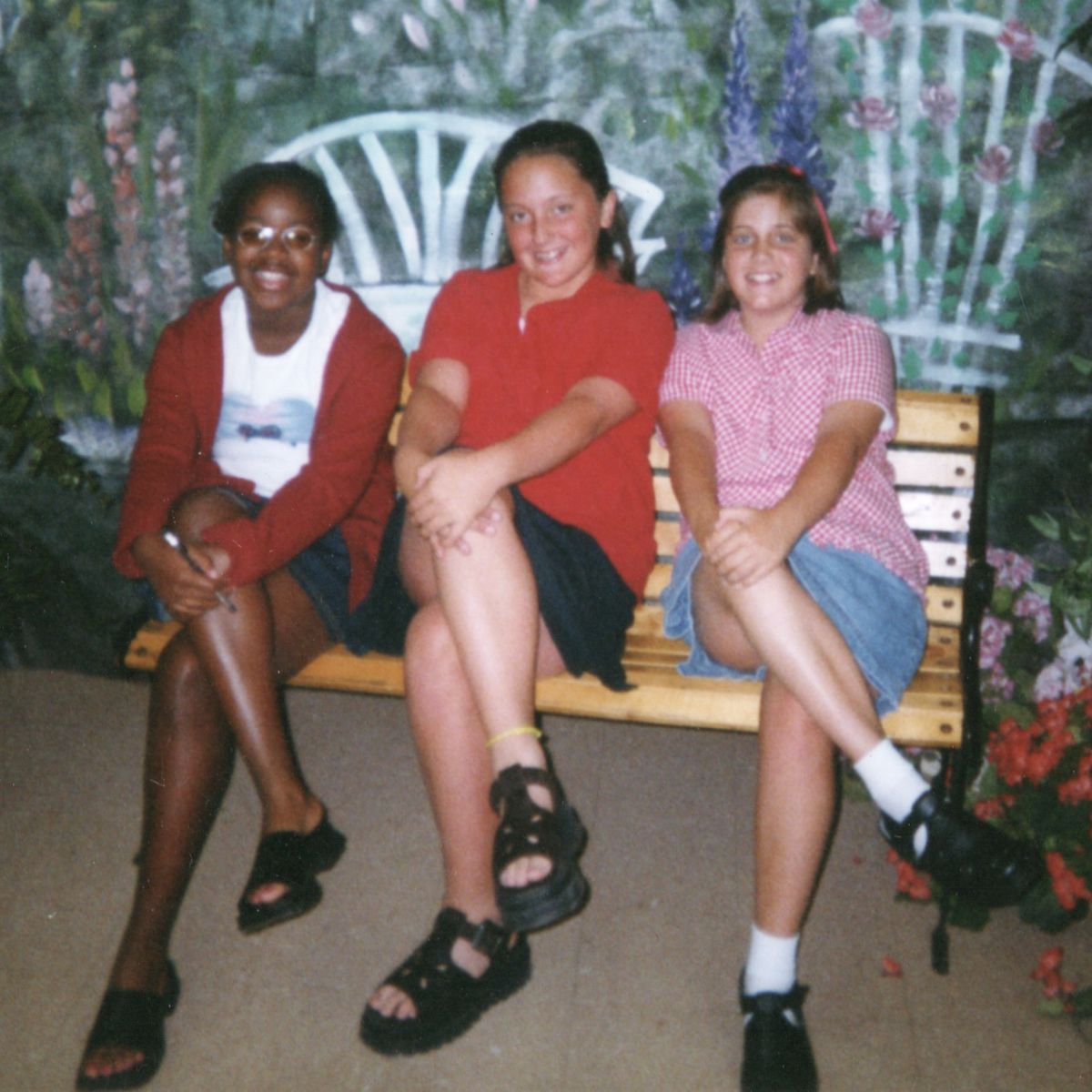 Three girls sit on a bench with their legs identically crossed, posing for a portrait together.