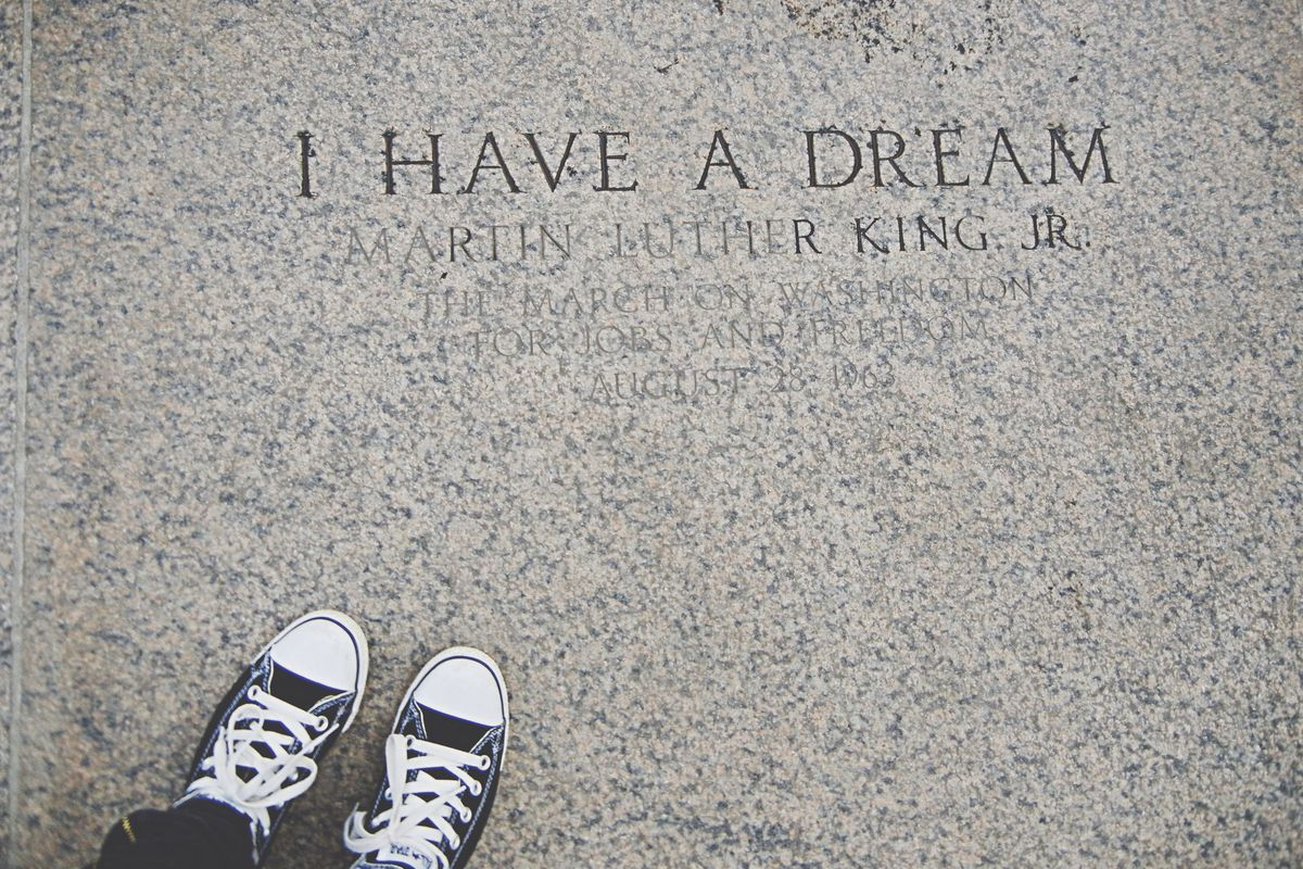 """A shot of someone standing near an engraving of """"I Have a Dream"""" and Martin Luther King Jr.'s name"""