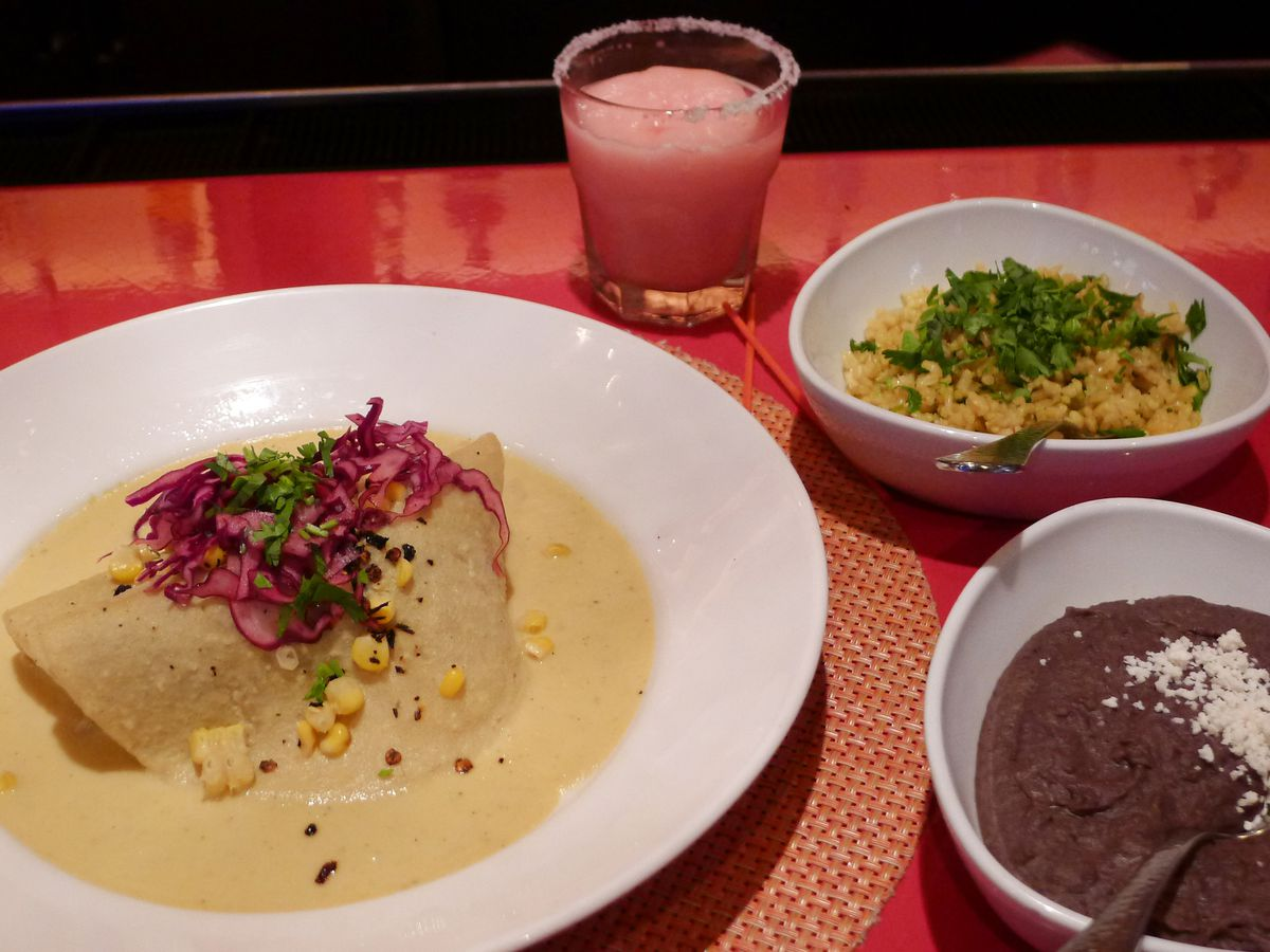 Several dishes on a red tablecloth with a pink frozen drink at the top.