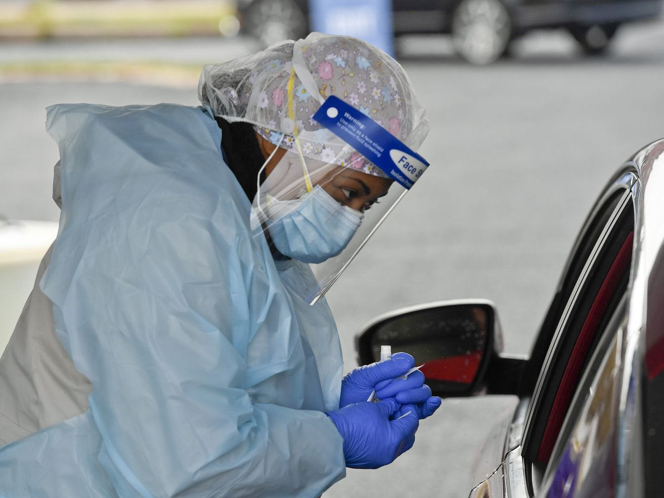 A Black woman in scrubs, a protective gown, medical cap, mask, and face shield, opens a vial with gloved hands. She appears to be speaking into the window of a car.