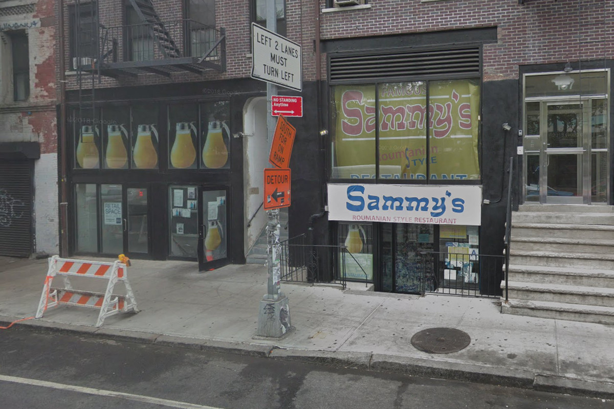 """An exterior of a restaurant with a white sign and blue lettering that reads """"Sammy's"""" above a basement-level entry door"""