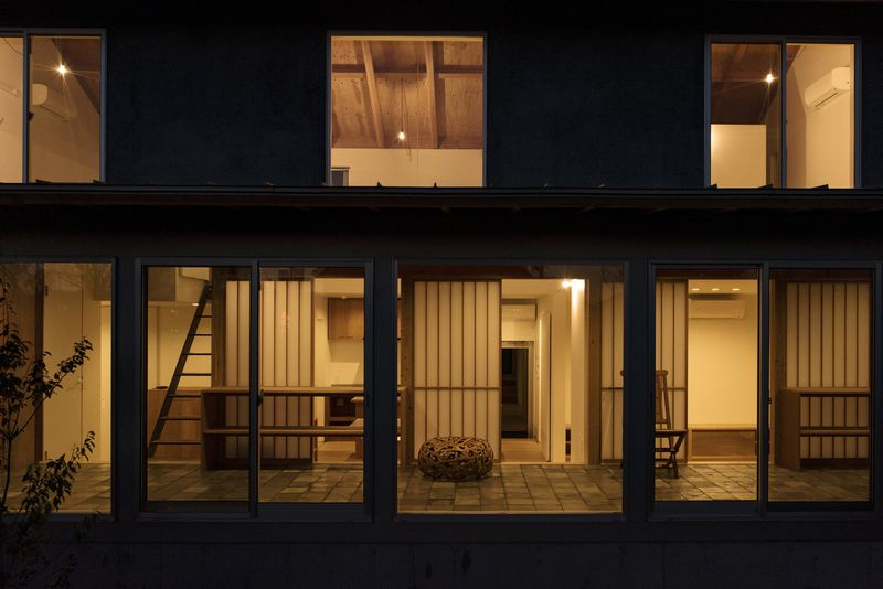 Exterior view of the house at night, with warm light coming from all rooms.