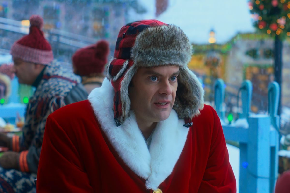 Hader, also dressed in red, looks dubious.