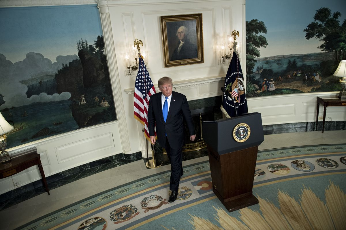 Donald Trump walks away from a podium, a portrait of George Washington looming behind him.
