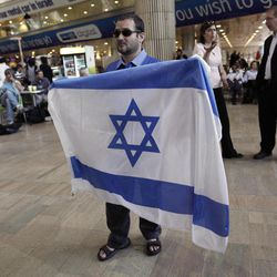 An activist holds an Israeli flag in protest against a pro-Palestinian campaign expected to arrive at Ben Gurion Airport near Tel Aviv, Israel, Sunday, April 15, 2012. Israel deployed hundreds of police Sunday at its main airport to detain activists flying in to protest the country's occupation of Palestinian areas, defying vigorous Israeli government efforts to block their arrival.