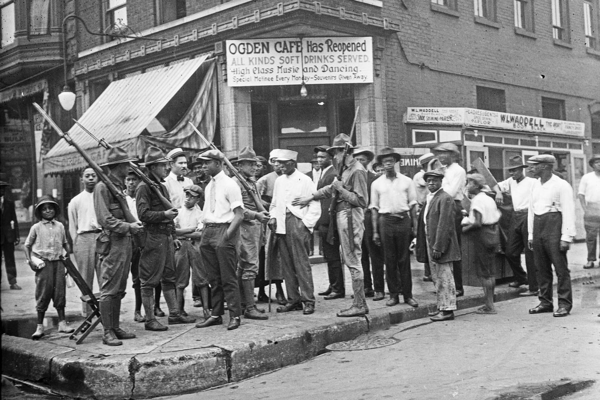 A crowd of men and armed National Guard soldiers stand outside a cafe during the 1919 Race Riots in Chicago.