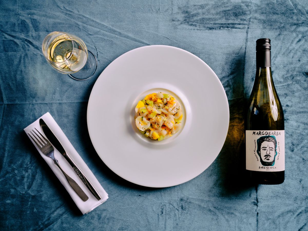 plate with raw fish and bottle of wine