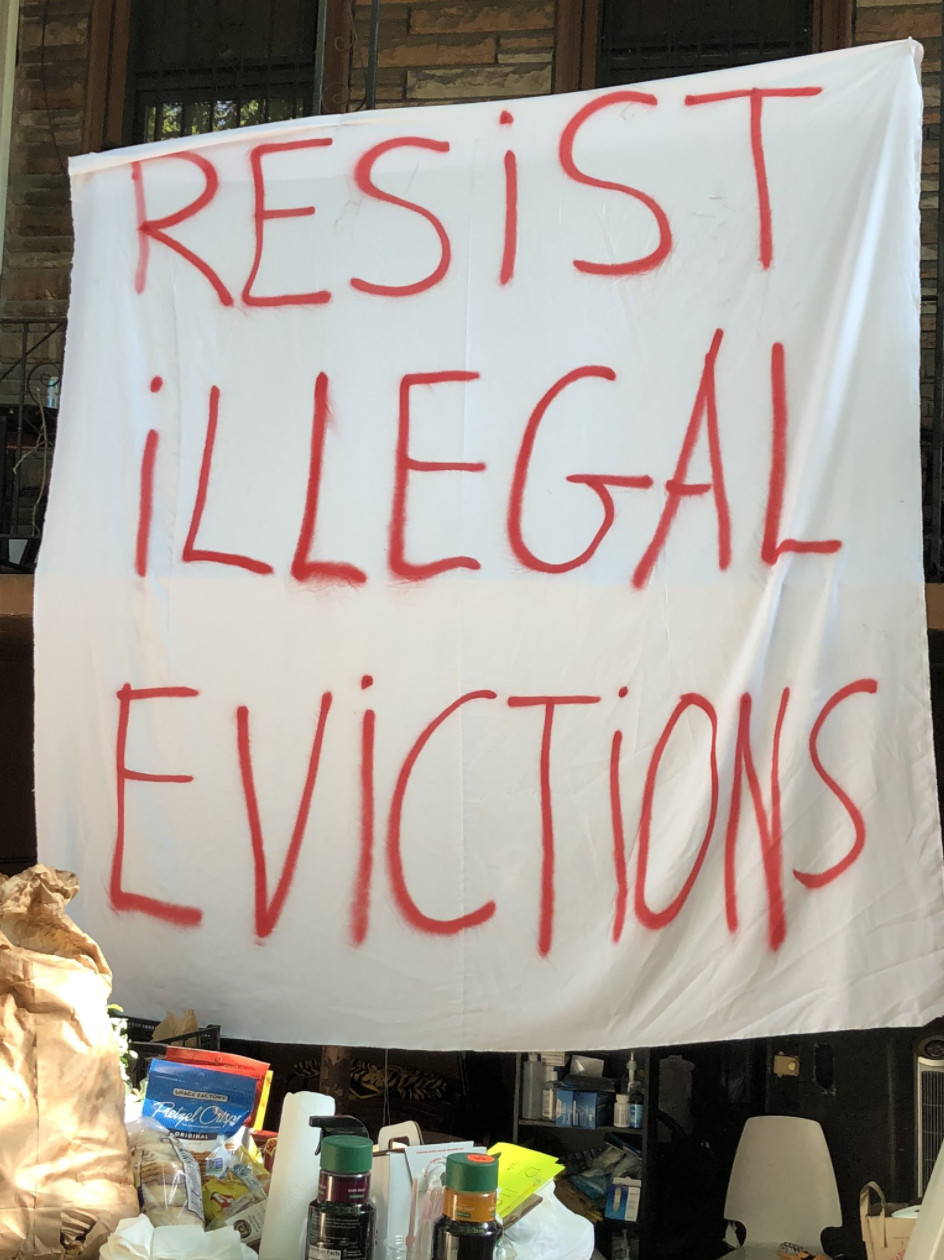 """A white banner spray painted in red lettering, """"Resist Illegal Evictions."""""""