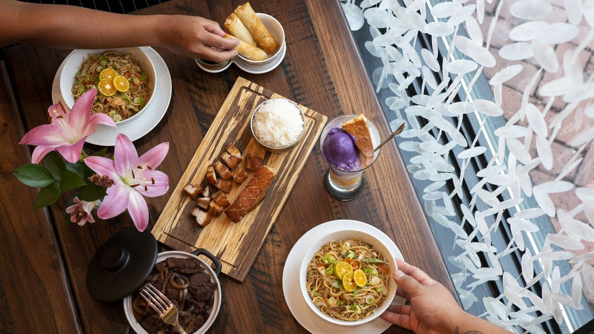 Five dishes on a dark wooden table set with a vase of hibiscus flowers at Estrellita in Grant Park with three people reaching to serve themselves