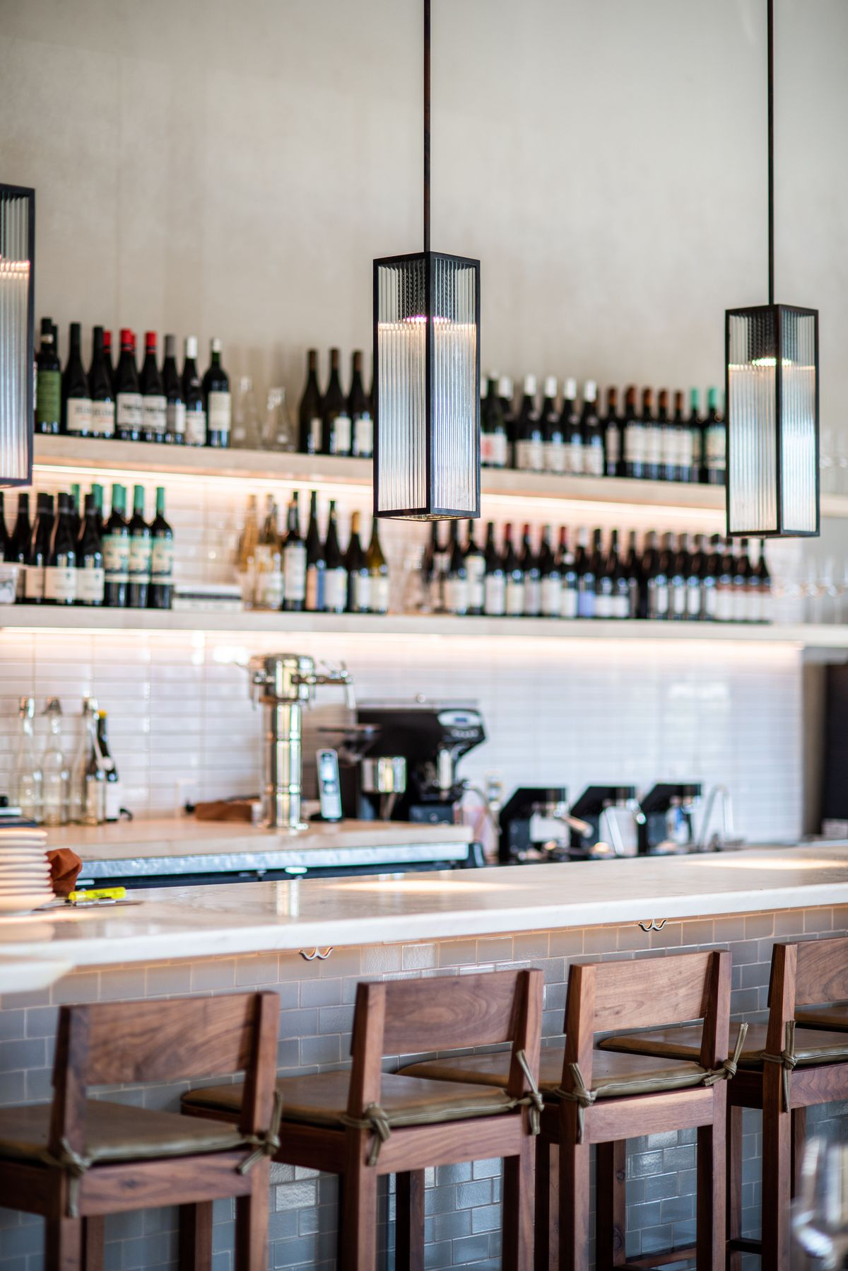 Bar with walnut stools and wine bottles at Varro.