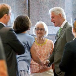 Former President Bill Clinton shakes hand with Alyson Heyrend and chats with former Utah first lady Norma Matheson as he arrives for a roundtable meeting with business leaders at the One Utah Center in Salt Lake City on Thursday, Aug. 11, 2016.