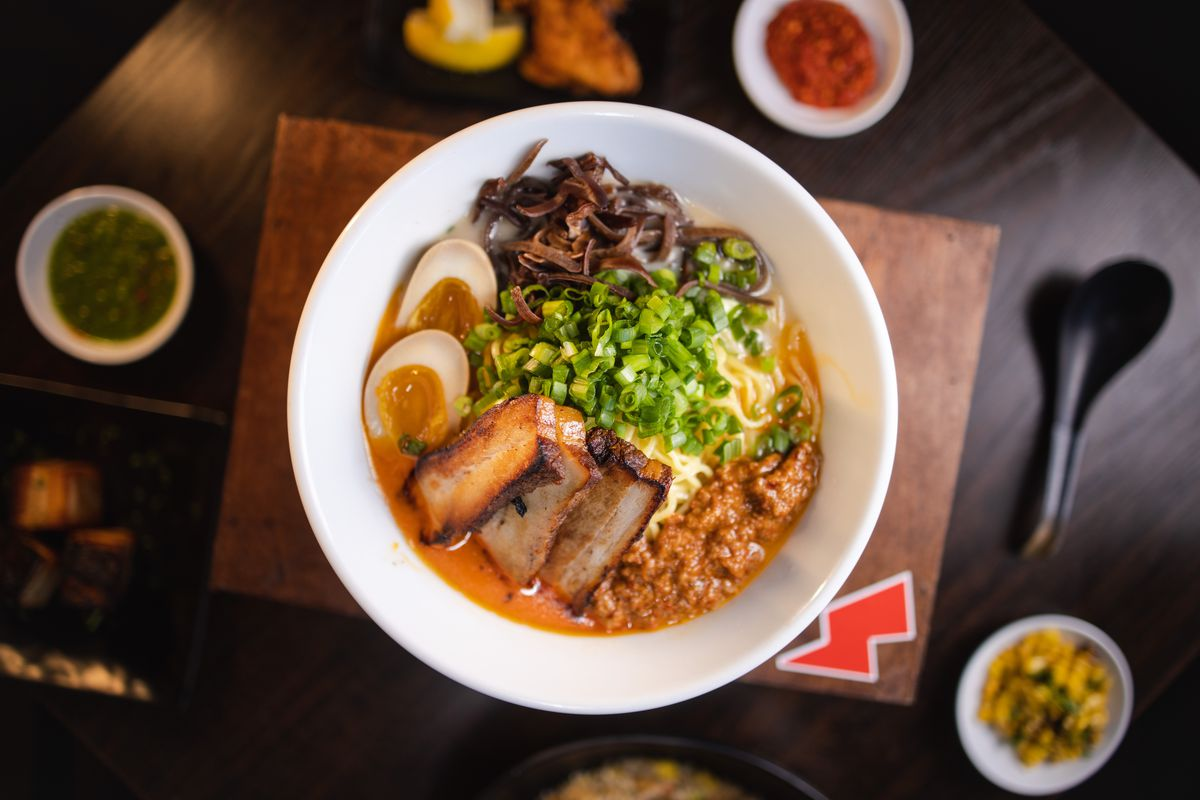 a overhead view of a bowl of ramen, with miso broth, boiled eggs, pork belly, green onions and mushrooms. The bowl is on a wooden cutting board