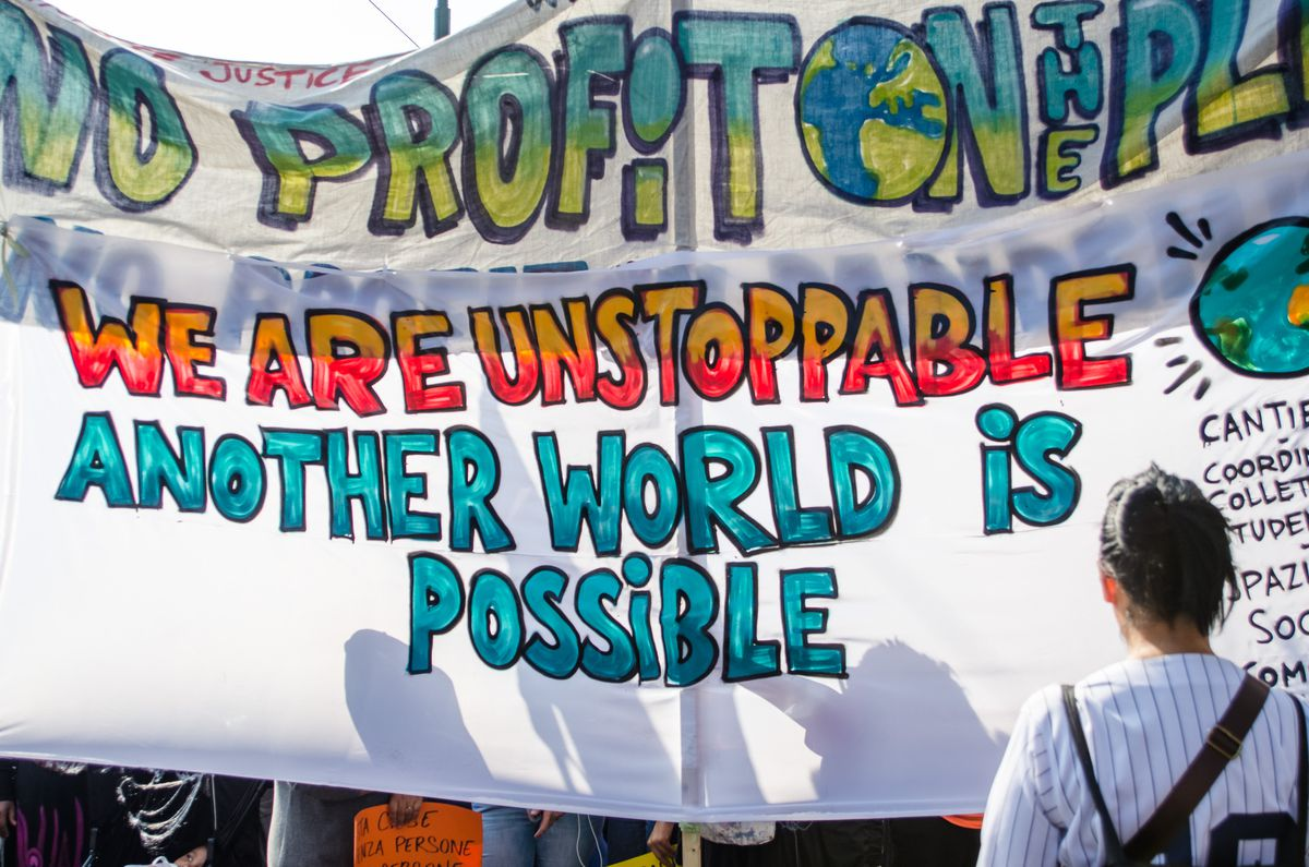 """A painted banner reads, """"No profit on the planet. We are unstoppable. Another world is possible."""""""