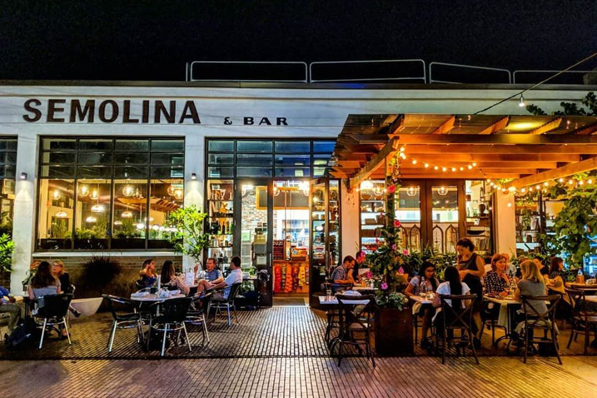 """Nighttime shot of the exterior of a restaurant, including an illuminated patio under wooden trellises. People are dining inside and out. Signage reads """"Semolina & Bar"""""""