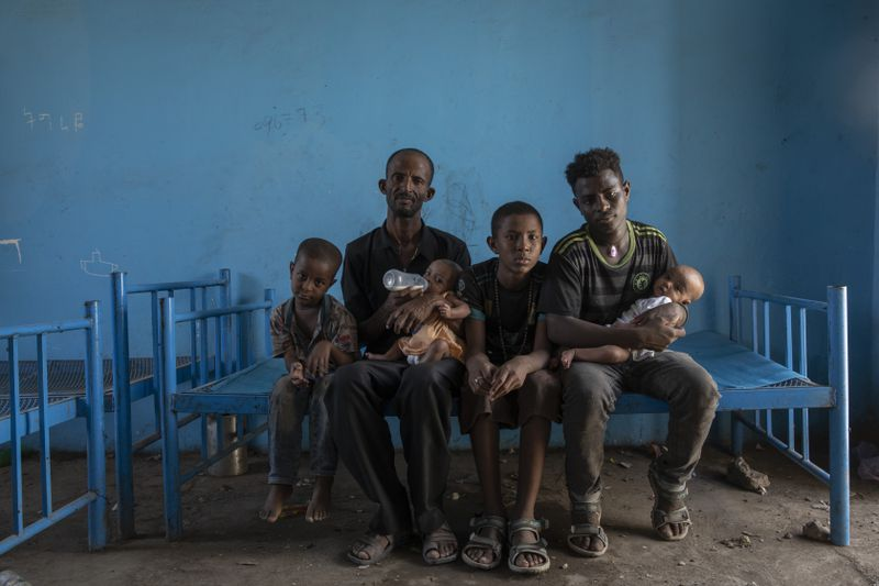 Abraha Kinfe Gebremariam, 40 (second from left) with his sons Micheale, 5 (left) and Daniel, 11 (center). his 19-year-old brother-in-law Goytom Tsegay (second from right) and his 4-month-old twin daughters Aden (right) and Turfu on his lap.