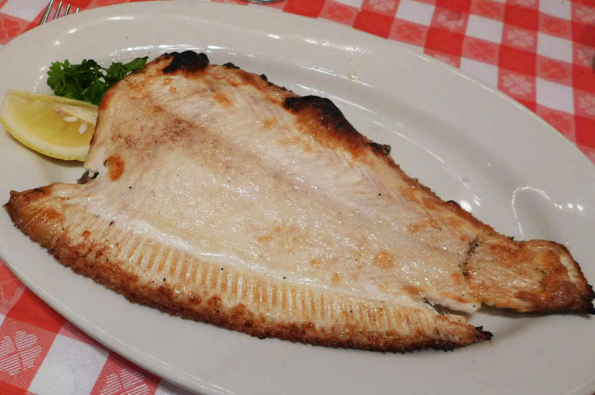 An entire headless fish that's been broiled, white flesh gleaming with a bit of brown on the edges...