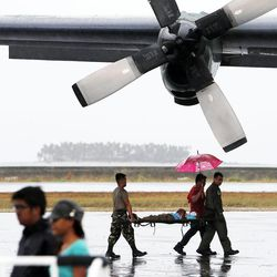 An injured person is brought to a transport plane leaving Tacloban, Friday, Nov. 22, 2013.