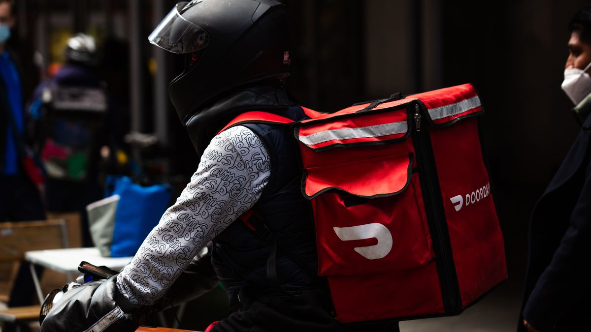 Closeup on a delivery person with a black motorcycle helmet and a Doordash backpack riding outside