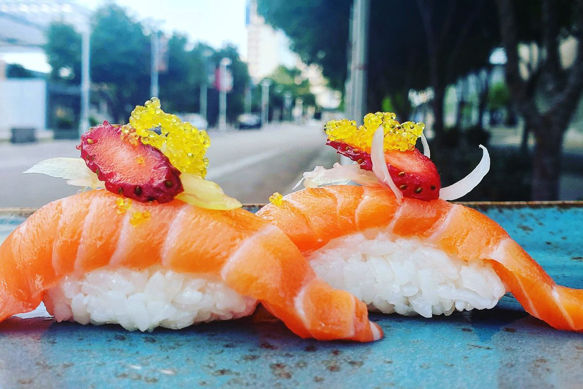 two pieces of salom sushi in front of a window overlooking a street