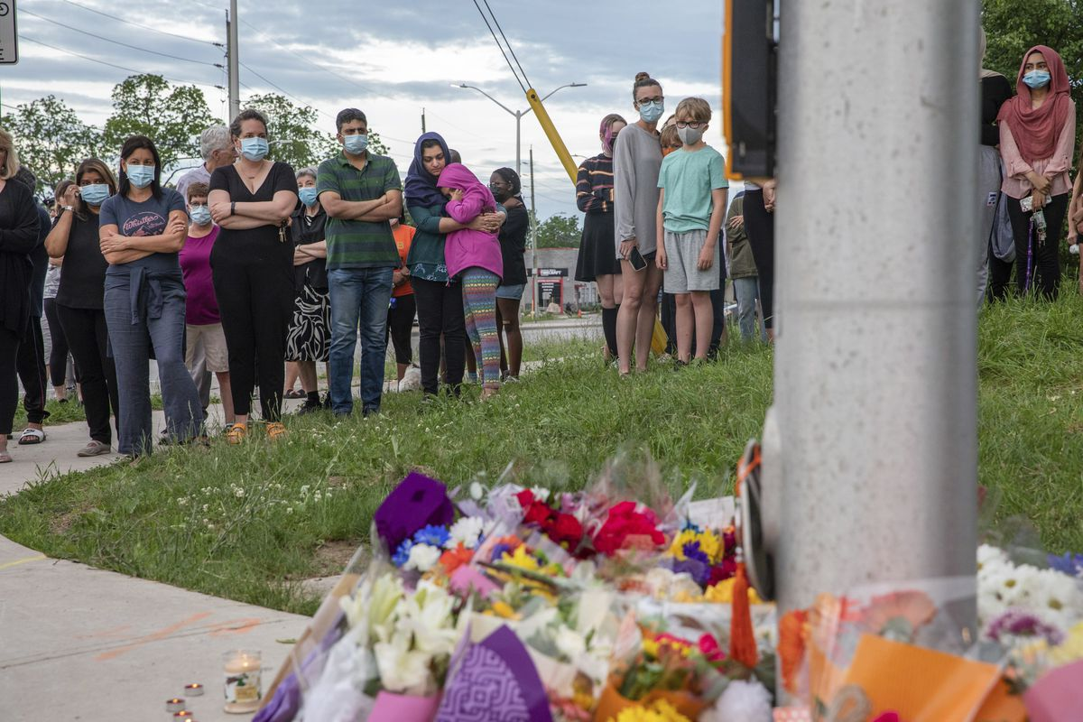 People attend at a memorial at the location where a family of five was hit by a driver, in London, Ontario, Monday, June 7, 2021. Four of the members of the family died and one is in critical condition. A 20-year-old male has been charged with four counts of first degree murder and count of attempted murder in connection with the crime.