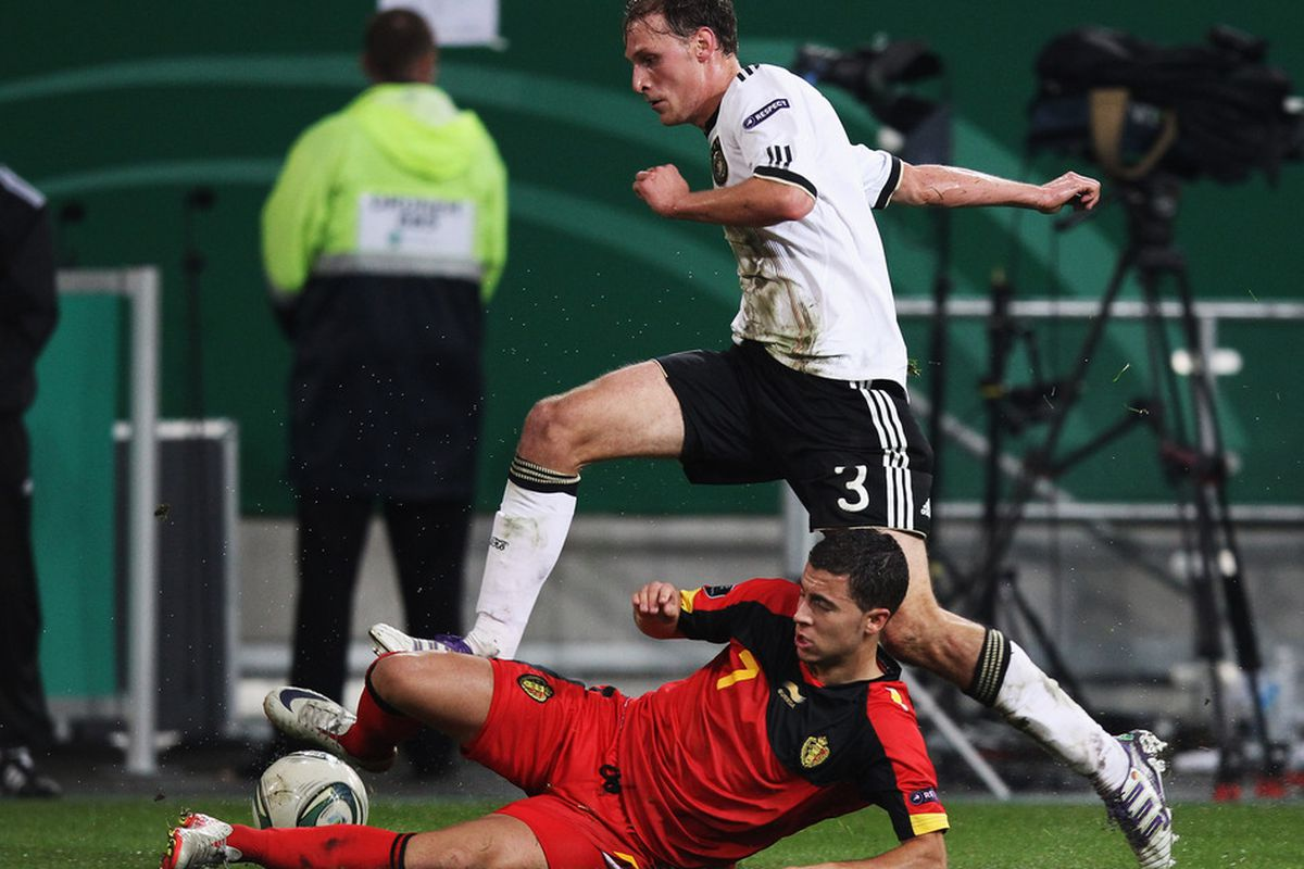 Beneditk Hoewedes of Germany battles for the ball with Eden Hazard of Belgium during the UEFA EURO 2012 Group A qualifying match between Germany and Belgium.