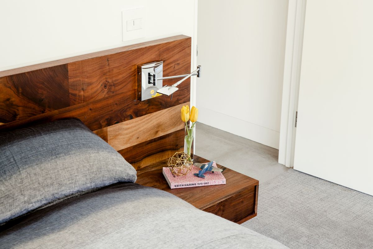 A detail of a custom walnut-wood bed. It has a wood headboard and built-in nightstand.