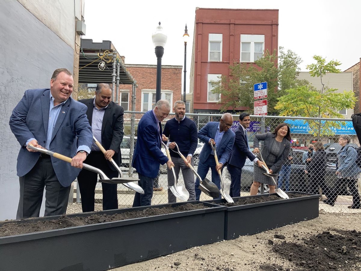 Ramova Shovel Shot: Together with city of Chicago and Cook County officials, Developer Tyler Nevius (center in blue sweater) celebrates McHugh Construction starting the restoration of the historic Ramova Theater and the construction of a new brewery and grill at 3510-3520 S. Halsted St. in Chicago's Bridgeport Neighborhood.