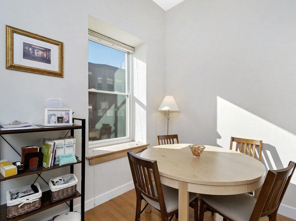 A corner of a condo with a table and four chairs.