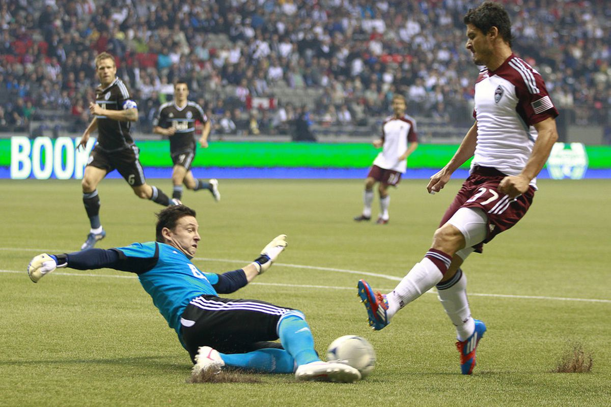 VANCOUVER, CANADA - JUNE 16:  Joe Cannon #1 of the Vancouver Whitecaps FC slides to make a save against Edu #37 of the Colorado Rapids during their MLS game June 16, 2012 in Vancouver, British Columbia, Canada. (Photo by Jeff Vinnick/Getty Images)