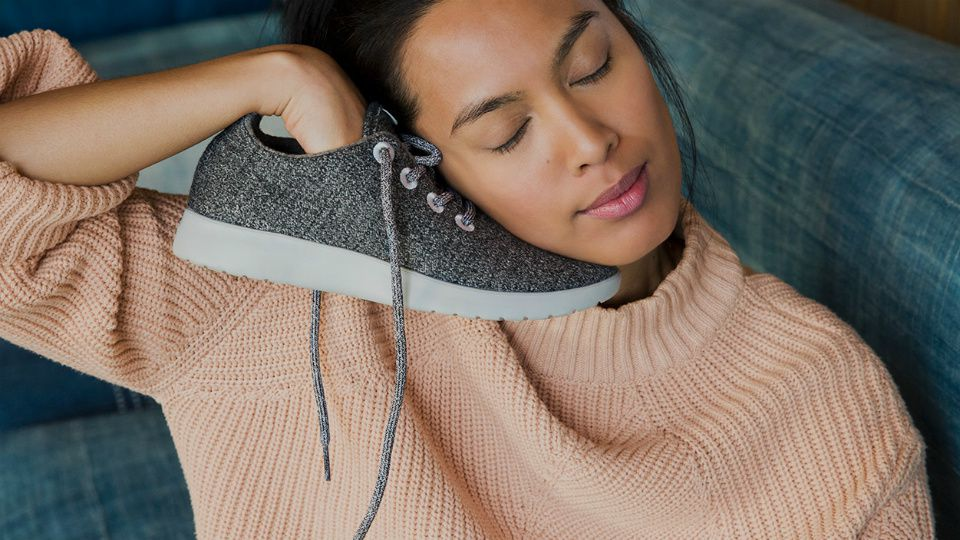 Woman holding Allbird sneaker up to face.