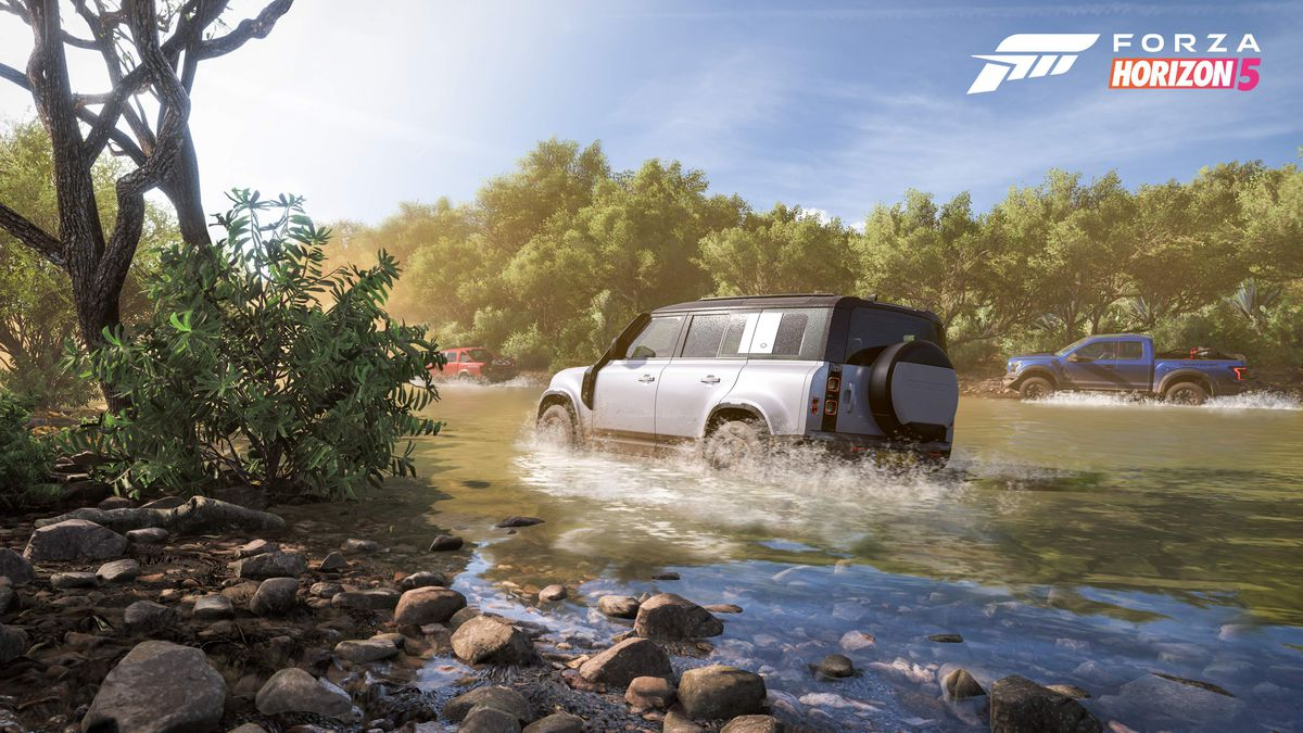 a sports utility vehicle and a pick-up truck race through a very shallow creek