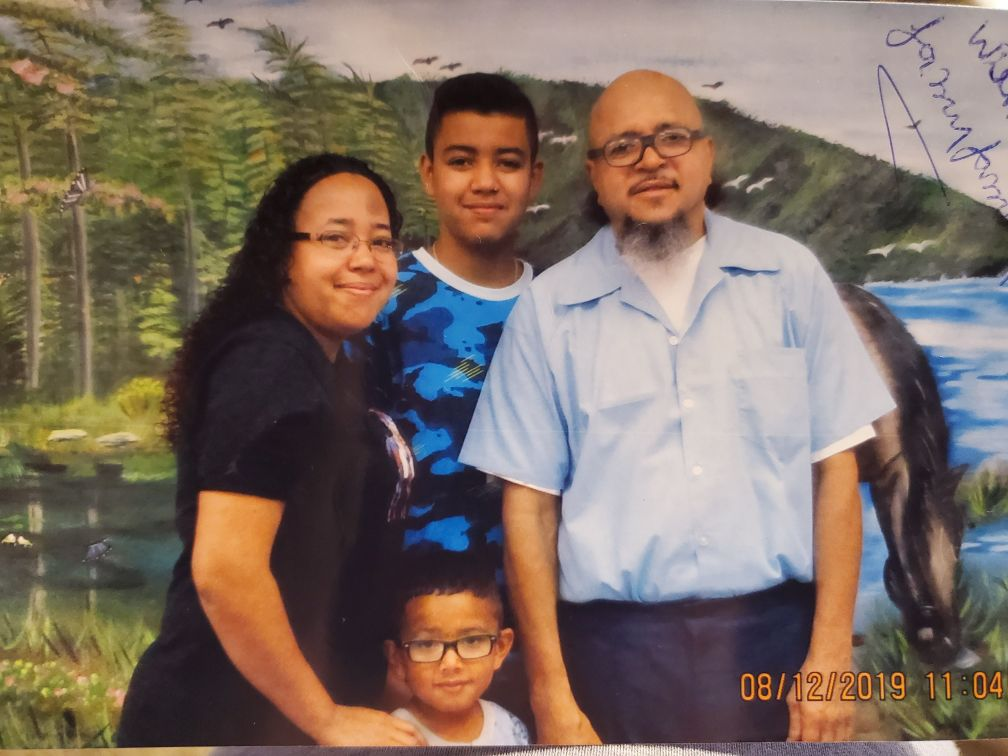 """Alfredo """"Freddy"""" Gonzalez poses against a backdrop at the Stateville Correctional Center, with his daughter, Maria and two of her sons."""