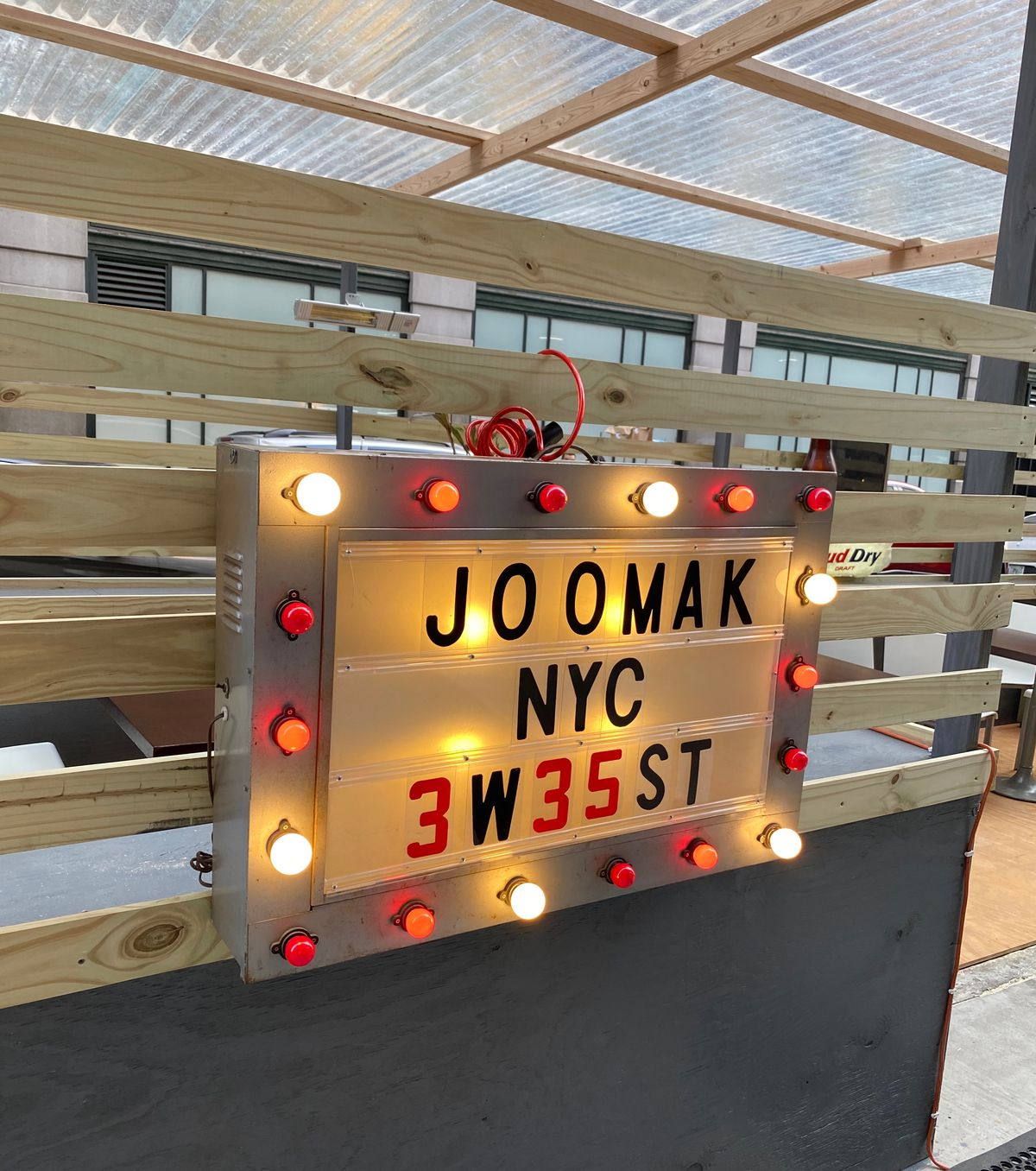 A sign with red and white neon lights that spells out Joomak hanging on wooden slats in front of an outdoor seating area
