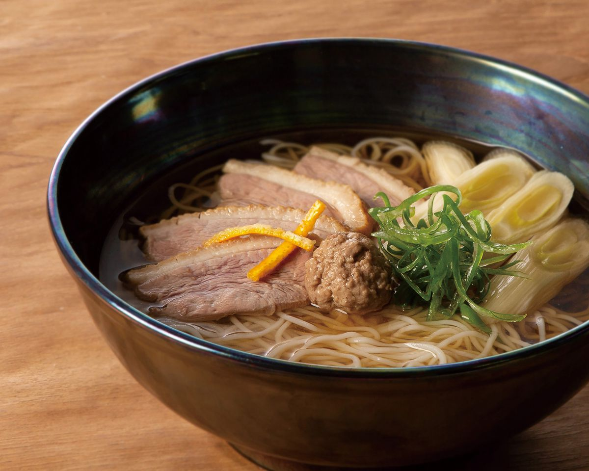 Slices of duck and leek float atop a bowl filled with delicate white noodles