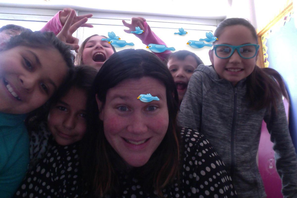Janine Logar takes a selfie with some of her students using an app that adds cartoons.
